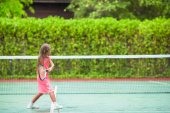 Little girl playing tennis on the court — Stock Photo