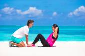 Young couple do abdominal crunches on white beach during vacation — Stock Photo
