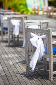 Wedding chairs decorated with white bows at outdoor cafe — Stock Photo