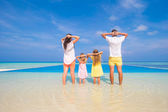 Rear view of young beautiful family on white tropical beach — Stock Photo