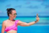 Young beautiful woman taking selfie with phone outdoors during beach vacation — Stock Photo