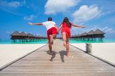 Młoda para na tropikalnej plaży molo na wyspie doskonały — Zdjęcie stockowe