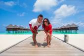 Young couple on tropical beach jetty at perfect island — Foto de Stock