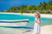 Adorable little girl with lollipop on tropical beach — Stock Photo