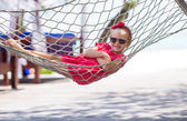 Adorable little girl on tropical vacation relaxing in hammock — Stock Photo