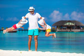 Happy father and his adorable little daughters at tropical beach having fun — Stock Photo