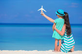 Young woman and little girl with miniature of airplane at beach — Foto de Stock