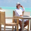 Business man calling by cell phone on white beach — Stock Photo #72431941