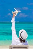 Young man with miniature of an airplane at tropical beach — Stock Photo