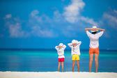 Adorable little girls and young mother on tropical white beach — Stock Photo
