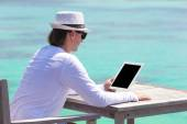 Young man with laptop at tropical beach — Stock Photo