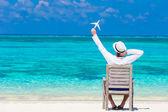 Giovane con la miniatura di un aeroplano alla spiaggia tropicale — Foto Stock
