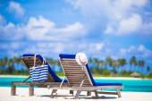 Lounge chairs with bag and hat on tropical white beach — Stock Photo