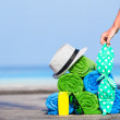 Beach and summer vacation accessories concept - close-up of colorful towels, hat, bag and sunblock — Stock Photo #73293215