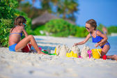 Little cute girls playing with beach toys during tropical vacation — Stock Photo