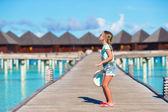 Очаровательны маленькая девочка, развлекаясь на деревянной пристани возле бунгало на воде — Стоковое фото