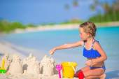 Adorable little girl playing with beach toys during tropical vacation — Stock Photo