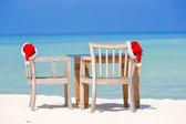 Red santa hats on beach chair at tropical vacation — Stock Photo