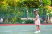 Little girl trying to play tennis on outdoor court — Stock Photo