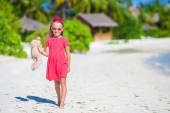 Adorable little girl playing with plush toy on beach — Stock Photo