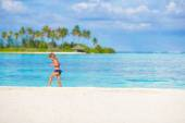 Adorable happy little girl have fun at shallow water on beach vacation — Stock Photo