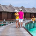 Young couple on beach jetty near water villa in honeymoon — Stock Photo #74945689