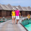 Happy couple on tropical beach jetty going to the beach at Maldives — Stock Photo #74945707