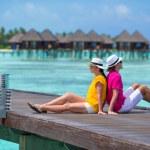Young couple on beach jetty near water villa in honeymoon — Stock Photo #74945865