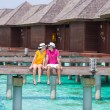 Young couple on beach jetty near water villa in honeymoon — Stock Photo #74948009