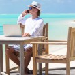 Young business man calling by cell phone on white beach — Stock Photo #74948615