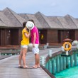 Young couple on beach jetty near water villa in honeymoon — Stock Photo #74948869