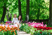 Adorable little girl and young mom enjoying warm day in tulip garden — Stock Photo