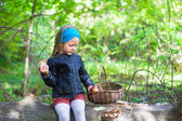 Little girl gathering mushrooms in autumn forest — Stock Photo