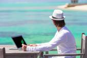 Young man with tablet computer on tropical beach — Stock Photo
