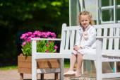 Liten bedårande flicka med blommor i tulpaner trädgård — Stockfoto