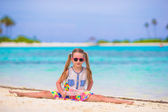 Adorable little girl have fun with lollipop on the beach — Stock Photo