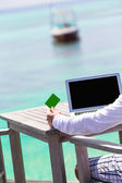 Close-up of green credit card and computer on table background the sea — Stock Photo