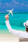 Back view of man with miniature of an airplane at tropical beach — Stock Photo
