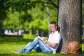 Młody człowiek relaks w pobliżu drzewa z kawy, czytanie książki — Zdjęcie stockowe