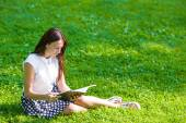 Young woman reading a book outside in park — Stock Photo