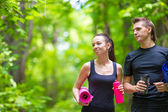 Jogging active couple have a rest with mat and bottle of water outdoors in forest — Stock Photo