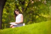 Jovem mulher relaxante com café no parque, ler um livro — Fotografia Stock