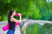 Young active fitness woman with mat and bottle of water outdoors — Stock Photo