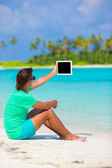 Young man working with laptop at tropical beach — Stock Photo