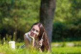 Умная женщина в парке за пределами запишите ее мысли в записной книжке — Стоковое фото