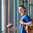 Young man holding passports and boarding pass at airport — Stock Photo #80820498