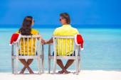 Young couple in Santa hats relaxing on beach during Christmas vacation — Stock Photo