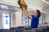 Young man putting luggage into overhead locker at airplane — Stock Photo