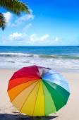 Rainbow umbrella by the ocean — Stock Photo