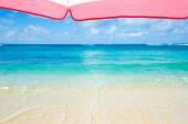 Beach umbrella next to ocean background — Stock Photo